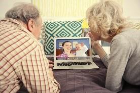 elder couple watching something on laptop